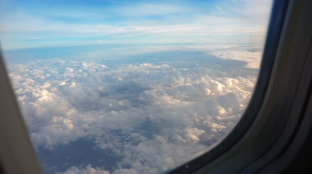 aircraft cabin : Above clouds, sky as seen in window of an aircraft