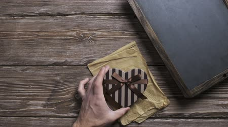 Mans hand puts heart shaped gift box to wooden desktop