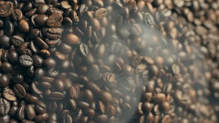 Roasted and smoking coffee beans. Vertical footage.