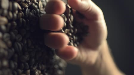 Coffee beans scatter out of males hand in slow motion