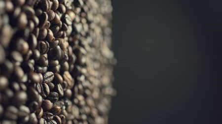Closeup of coffee beans fall down in slow motion