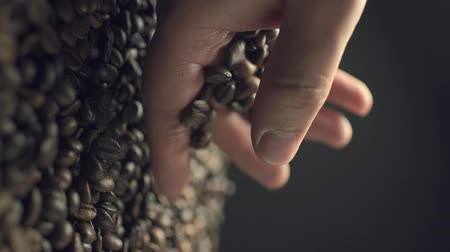 scatters : Closeup of coffee beans scatter out of males hand in slow motion Stock Footage