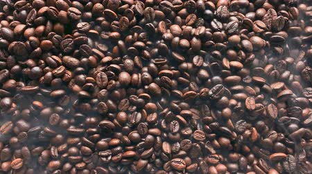 tahıllar : Smoke swirls over hot coffee beans. Top view. Stok Video