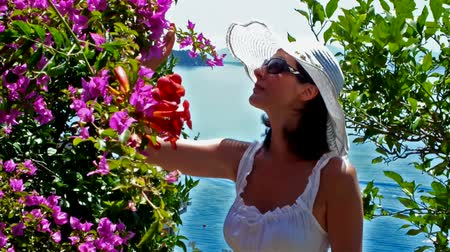 giydirmek : Woman in summer garden; Women enjoy the smell of flowers in the sunny Mediterranean summer garden,video clip