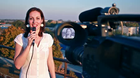 вещание : TV reporter on assignment ; TV reporter in front of the camera gives notice of the weather forecast at the top of the building,video clip