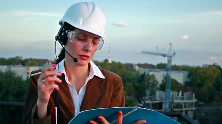 только один человек : Female construction engineer reading plans and talk to workers through internal links,video clip