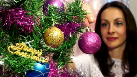 zvyk : Decorating the Christmas tree ; Beautiful and smiling young woman decorates Christmas tree, video clip