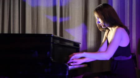 fortepian : piano player ; young woman playing a grand piano