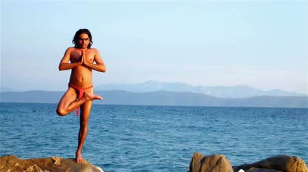 gimnastyka : Yoga on the sea cliff ; yoga instructor from India demonstrates exercises of yoga on the beach,video clip Wideo