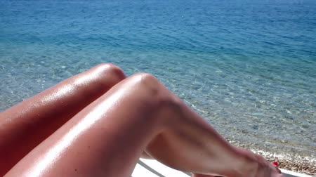 opalenizna : Sun,sea and beach ; beautiful tanned womens legs at the beach,video clip