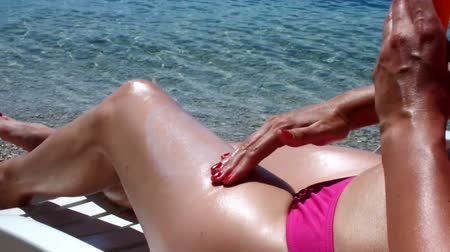 banhos de sol : Protection from the sun ; pretty woman is embellishing protective cream on the beach,video clip