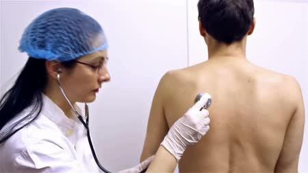 грипп : Doctor and patient ; doctor examines a patient with a stethoscope,video clip