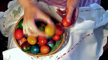 koszyk wielkanocny : basket full of colorful eggs ; female hand puts in a basket wonderful decorated colorful Easter eggs,video clip