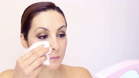 tükör : A beautiful young woman removing makeup from the face with a white cotton wool, Make-up, video clip