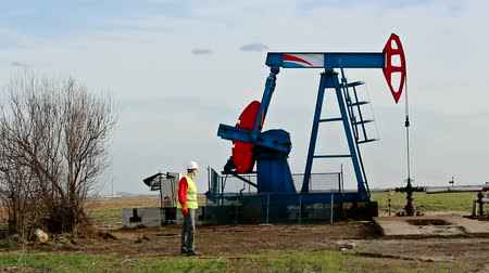 petrokimya : Worker on an oil rig ; Oil worker controls the operation of the oil pump,video clip