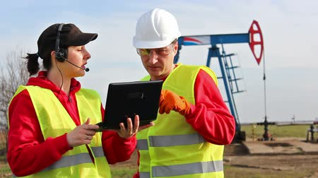 petrokimya : Engineers in the oil field ; Male and female oil engineers discuss and control the work of the oil pump with a laptop,video clip