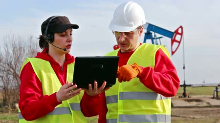 oliwa : Oil wells ; Male and female oil engineers discuss and control the work of the oil pump with a laptop,video clip