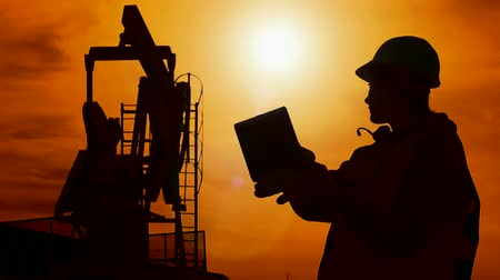 petrokimya : Silhouette worker and oil pump ; Silhouette worker-engineers which controls the oil pump with a laptop ,against the sunset,video clip Stok Video