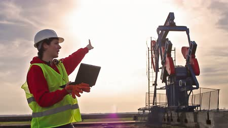 praca : Oil worker and pump jack ; Oil worker controls the operation of the oil pump,video clip