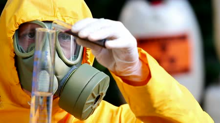 safeness : Chemist with a gas mask ; Chemist with the gas mask and the protective suit examining toxic supsance,video clip