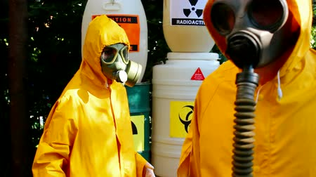 safeness : Work with hazardous materials ; Two chemical technicians with gas masks and protective suits carried out disposal of toxic substances,video clip