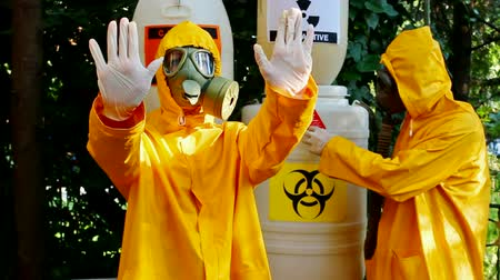 biztonság : Toxic waste ; Two chemical technicians with gas masks and protective suits carried out disposal of toxic substances,video clip Stock mozgókép