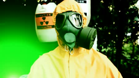 safeness : Dangerous radiating;Chemist in protective clothing with gas mask gives a warning sign, fly cam video clip