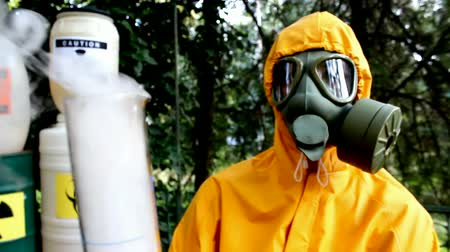 safeness : Chemical reaction with dangerous substances ; Chemical technician in a protective suit and gas mask performs testing of dangerous substances,video clip Stock Footage