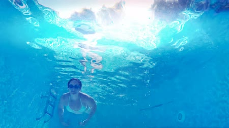 underwater video : Girl diving in the pool ; Young woman swim and dive in the beautiful swimming pool, underwater video clip