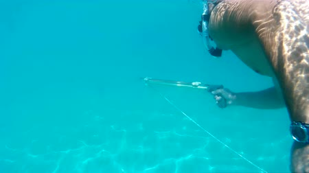 spear gun : Diver with underwater gun ; Diver with underwater gun and harpoon diving into the depths of the sea,video clip