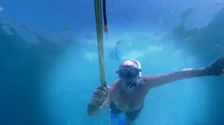 spear gun : Underwater fisherman ; Diver fires a harpoon for underwater fishing directly into the camera,video clip Stock Footage