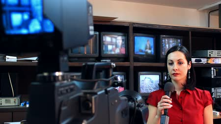 вещание : Preparations for the inclusion of live TV ; Beautiful newscaster is preparing to publish the latest news, while the cameraman adjusts broadcasting equipment,video clip