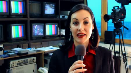 into focus : TV reporter in studio ; Beautiful newscaster announces the latest news in the television studio,video clip