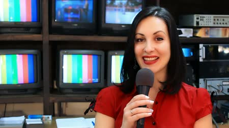 camera operator : TV reporter in front of the studio camera ; Beautiful newscaster presenting news in TV studio,video clip Stock Footage
