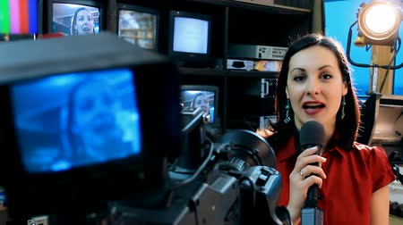 into focus : TV presenter latest news ; Beautiful newscaster presenting news in TV studio,video clip Stock Footage