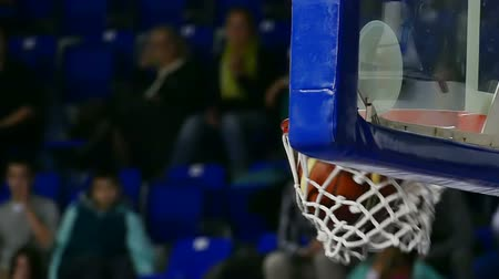 баскетбол : Basketball Hoop during the match ; Basketball falls through hoop, slow motion video clip Стоковые видеозаписи