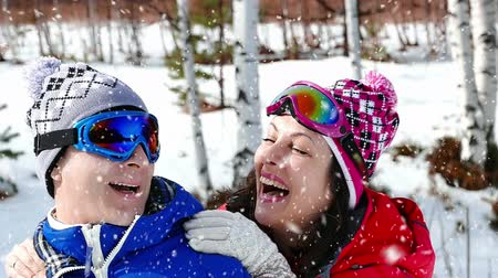 smích : Happiness and laughter while snowing ; Pair of skiers hugging and looking forward to the snow,slow motion video clip