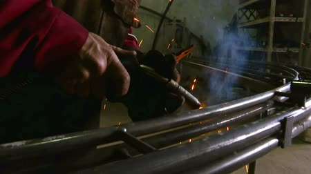 fire facilities : Gas welding a metal pipe ; Welder performs gas welding of metal construction in the workshop , video clip Stock Footage
