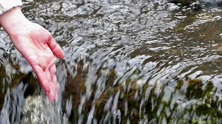 engulfed : Woman hand in water clear mountain river ; Womans hand is engulfed pure water from the mountain river,slow motion video clip