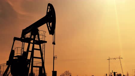 petrokimya : Pump Jack at Dusk ; Working oil pump silhouette against sunset