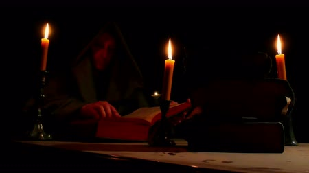 cassock : Old Church Books in the Hands of Monk ; Monk reads the old liturgical book in the monastery cell under candlelight Stock Footage