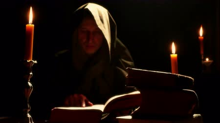 cassock : Monk at the Monastery with the Old Liturgical Books ; Monk reads the old liturgical book in the monastery cell under candlelight