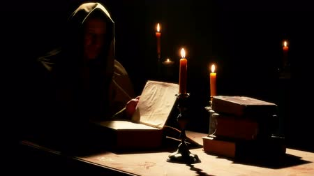 cassock : Monk reads the Old Liturgical Book ; Monk reads the old liturgical book in the monastery cell under candlelight