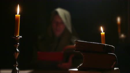 cassock : Monk Studying Old Religious Books ; Monk reads the old liturgical book in the monastery cell under candlelight
