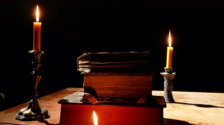 cassock : Ancient books on the table by candlelight ; Old books on the table monastery Reading Room lighted candlelight