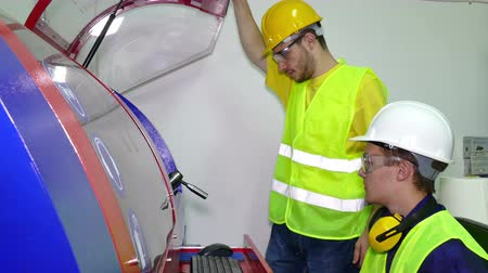 mecânica : Young workers in the machine room ; The machine technician performs computer control of the working machine Stock Footage