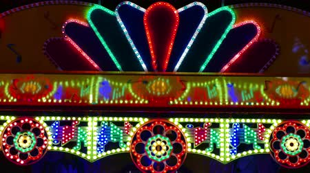 searchlight : Blinking Multicolored Bulbs on a Large Panel ; A vibrant flickering of a multicolored light on an electric advertisement in an amusement park