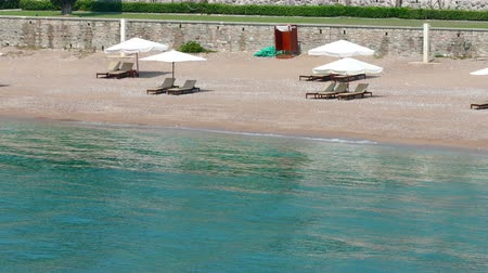 bab : Sunshades on a Sandy Beach ; View of the beautiful Saint Stephens beach in Montenegro