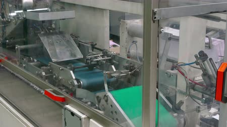 nejlon : Automated Machine for Packing Nylon Stockings ; Machine in the process of producing and packing womens nylon stockings