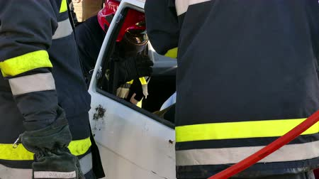 first officer : Zrenjanin ; Serbia ; 22.11.2017.  Firefighters rescuer team breaks car glass to save injured driver-demonstration exercise.